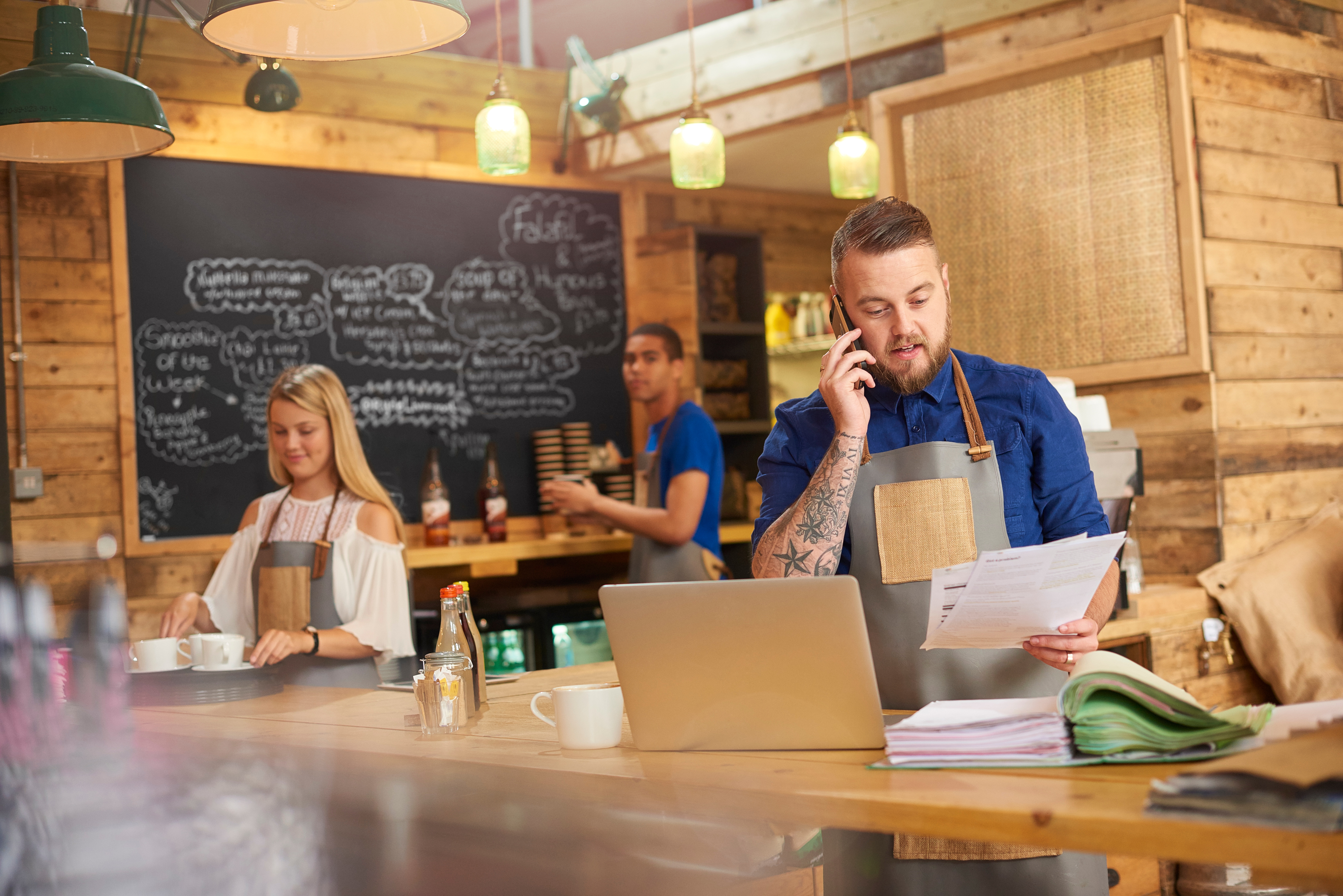 Coffee-shop-owner-phoning-accountant-597272594_7360x4912