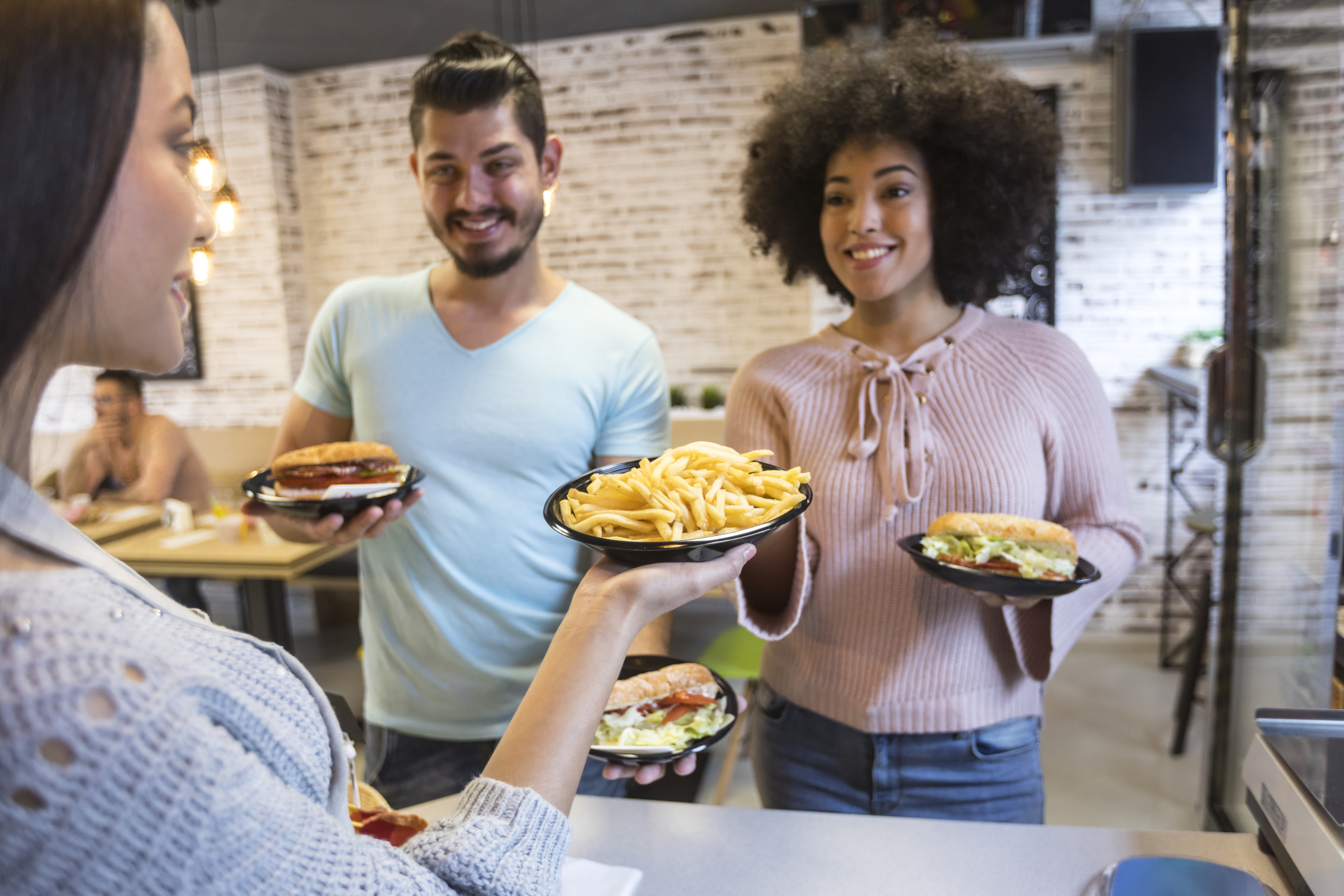 Couple-in-fast-food-restaurant-buying-burgers-937358382_6720x4480