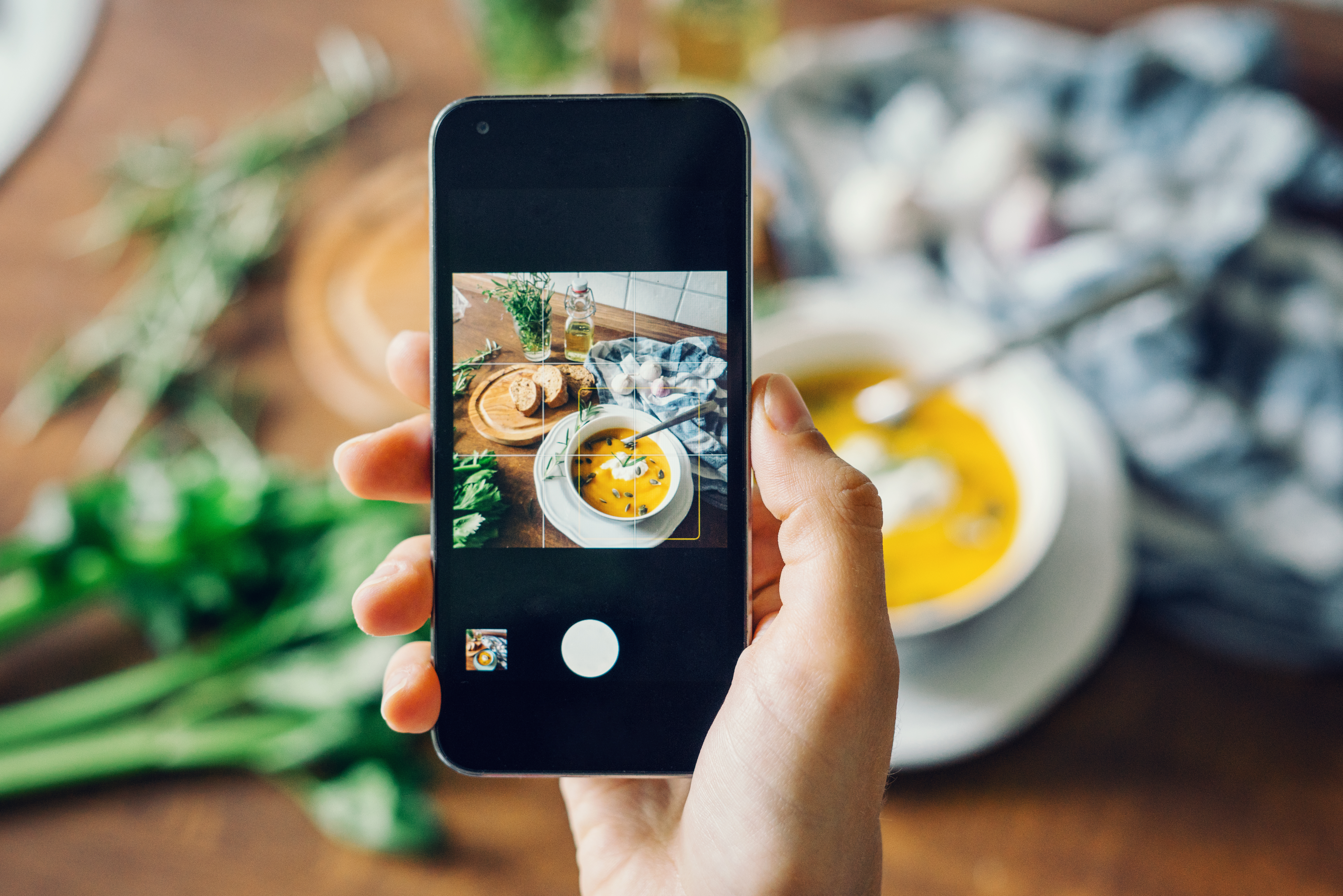 Woman-taking-photo-of-pumpkin-soup-with-smartphone-624718052_7360x4912