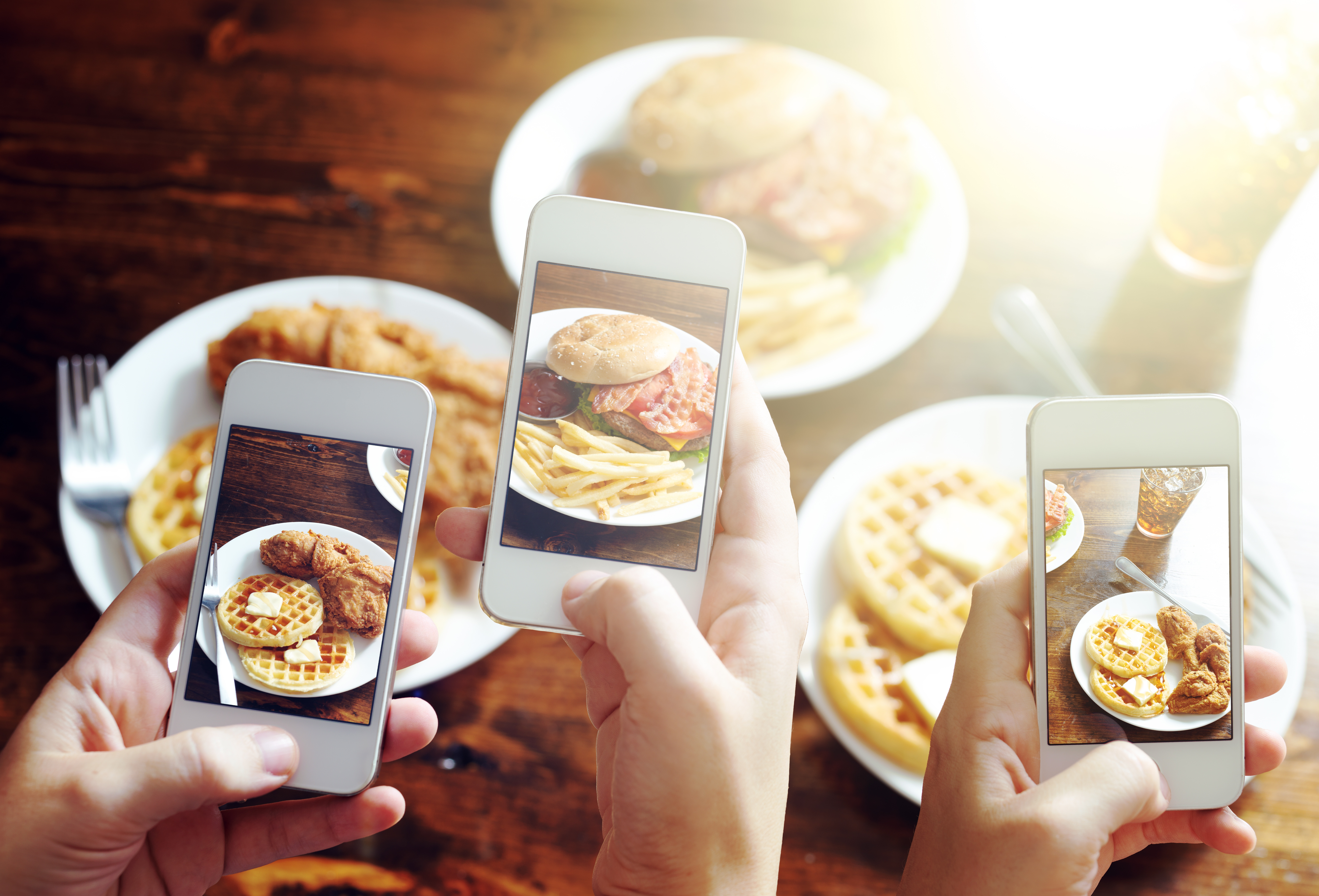 friends-taking-photos-of-food-with-smart-phones-508631655_7555x5130